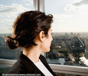 Picture of a woman looking out a window from high above a city. The woman has short brown hair pulled back. Dark coat over a white blouse. Beautiful scenic view of Buenos Aires out the windows.